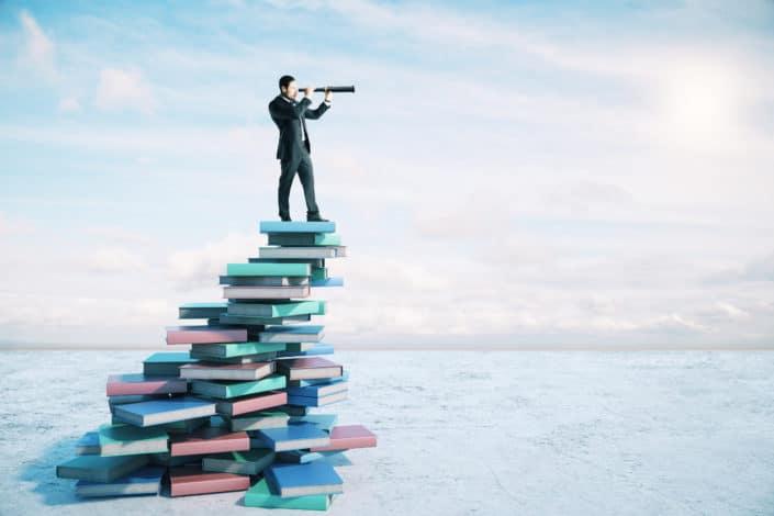 man standing on books