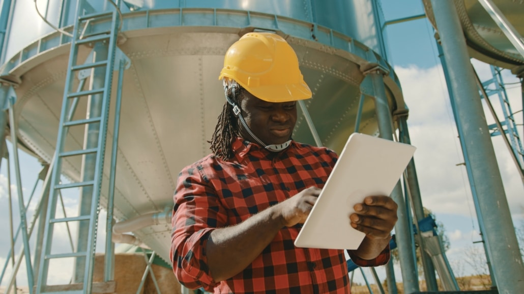 Young,Handsome,African,Man,,Engineer,With,Safety,Helmet,Using,Tablet